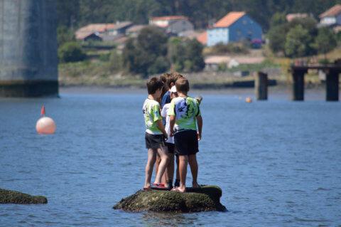 Mozos piragüistas sobre unha roca
